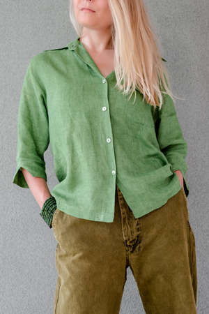 Artistic young woman with blonde hair, wearing green clothes. Foto de archivo