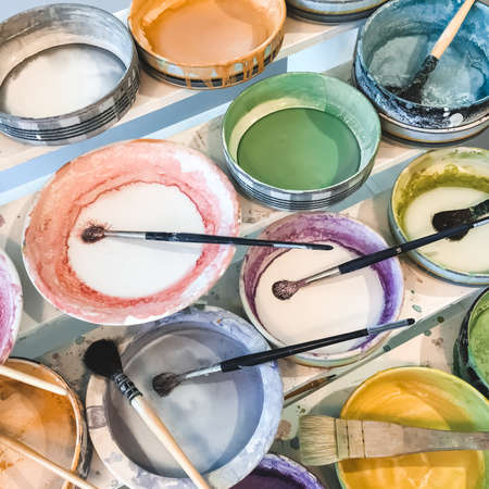 Paint and paintbrushes in colorful ceramic plates.
