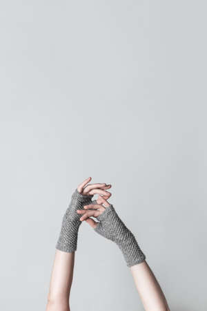 Elegant female hands in gray knitted gloves, on neutral background with copy space. Standard-Bild - 141185050
