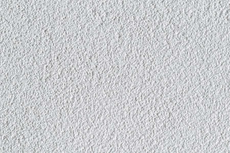 Textured white wall of an urban building.