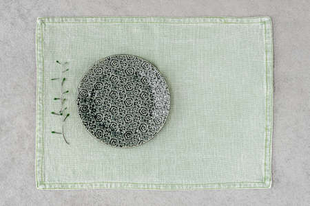 Green ceramic plate with floral design on linen placemat.