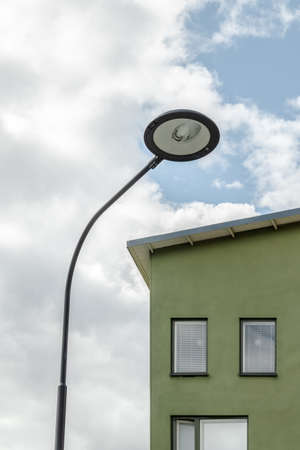Streetlamp and European style facade of a green residential building. Stock fotó