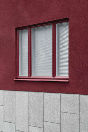 Window with closed blinds. Close-up of a modern building with red and gray walls.