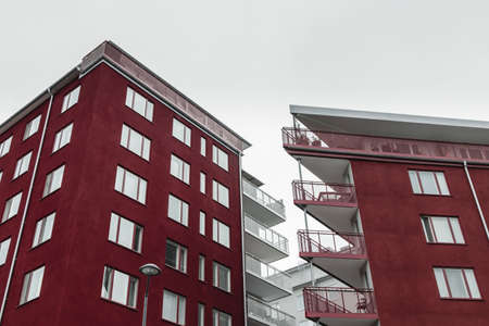 Corners of modern dark red buildings with balconies against cloudy sky. Stockholm, Sweden. Standard-Bild - 141185057