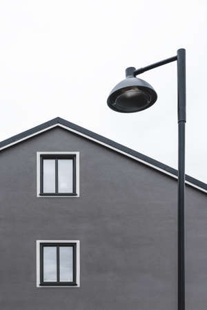 Streetlamp and European style facade of a house with two windows.