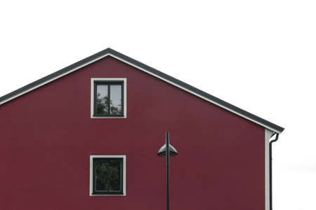 Streetlight in front of a modern cherry red house, against white sky background.