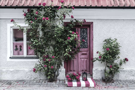 Picturesque house entrance decorated with roses, in the town of Visby (Gotland, Sweden). Banco de Imagens
