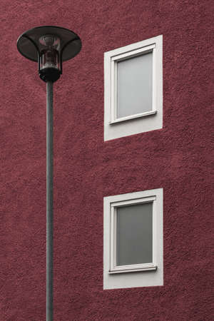 Streetlamp in front of a dark red residential building with white windows. Standard-Bild - 141185061