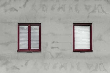 Close-up of a simple gray house with red window frames. Standard-Bild - 141185063