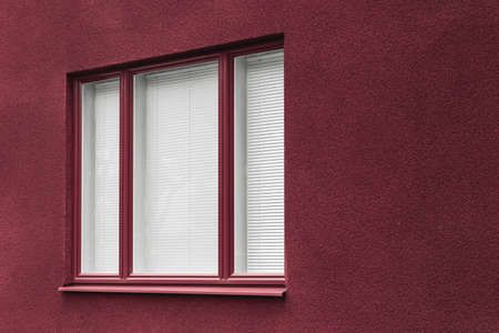 Window and wall of a cherry red modern building with closed blinds for privacy. Banco de Imagens