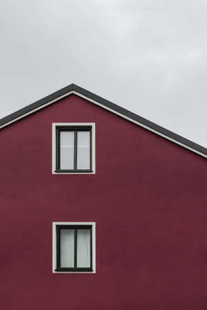 Facade and roof of a dark red house with white windows, against cloudy sky.