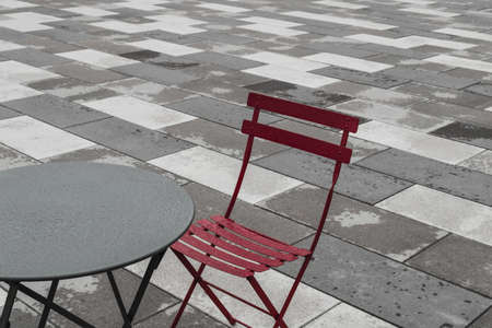 Outdoor cafe with red chair and round table, after the rain.