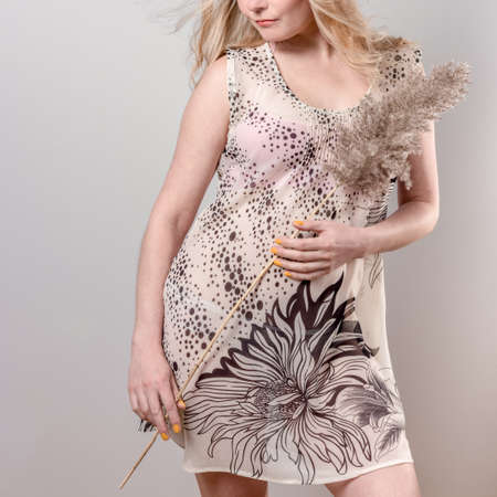 Blonde girl in pink dress holding ornamental pampas grass.