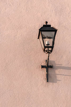 Old streetlight on a textured pink wall with copy space.