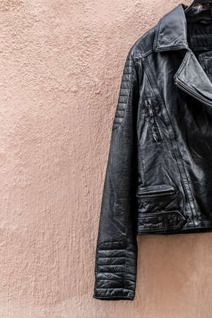 Black leather jacket on pink wall with copy space. Standard-Bild