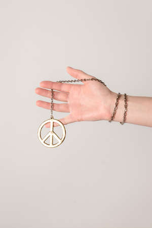 Female hand holding a golden peace sign, on neutral background with copy space. Standard-Bild - 141304863