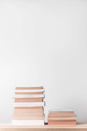 Stacks of books on a wooden shelf, on neutral background with copy space. Standard-Bild - 141424903