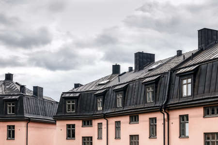 Pastel colored residential buildings with black roofs. Stockholm, Sweden. Standard-Bild