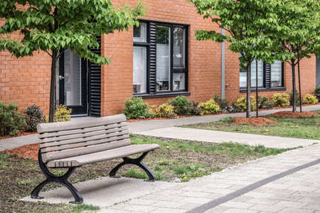 Bench in front of a modern brick building. Green city neighborhood in spring.