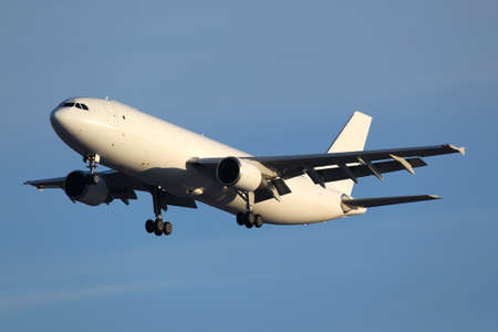 civil cargo airplane landing in airport. Stock Photo