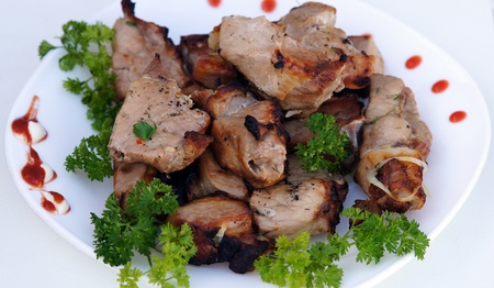 Fried meat and barbecue, with the green of the parsley on a white background
