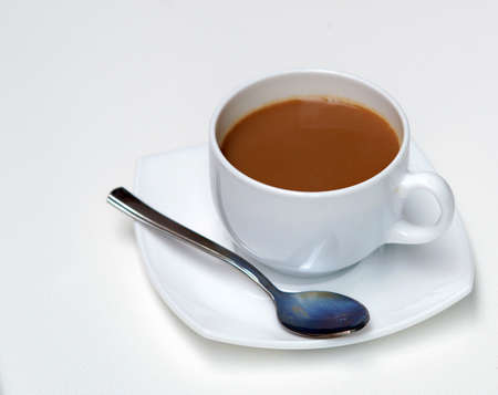 A spoon and a cup of hot coffee with milk in a white Cup,with a white saucer on a white background