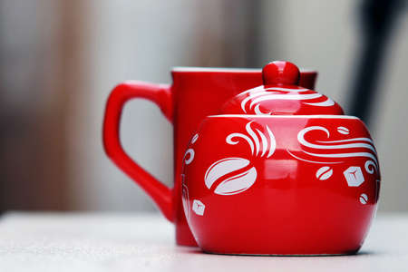 Porcelain red sugar bowl and a mug for coffee or tea