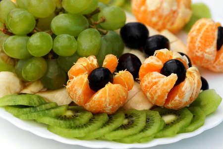 Grapes,kiwi,bananas,tangerines on white plate