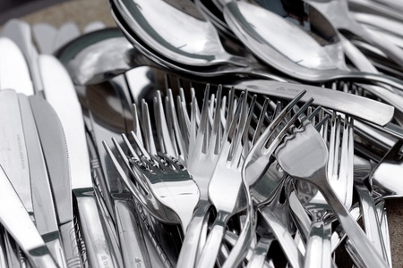 Spoons,forks and knives lying on a tray