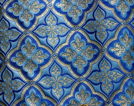 Large bright,silvery pattern on a blue background fabric.