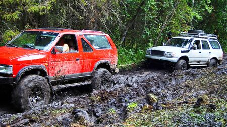 sport utility vehicle: Red SUV pulls out a white sport utility vehicle that is stuck in the mud.