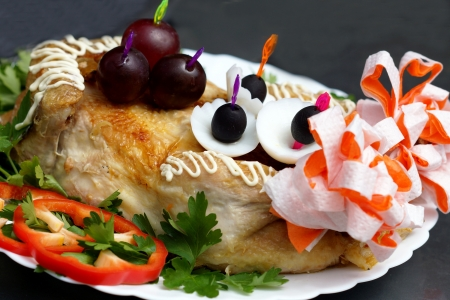 Fried chicken on a white plate,decorated with parsley, grapes and slices of sweet pepper.