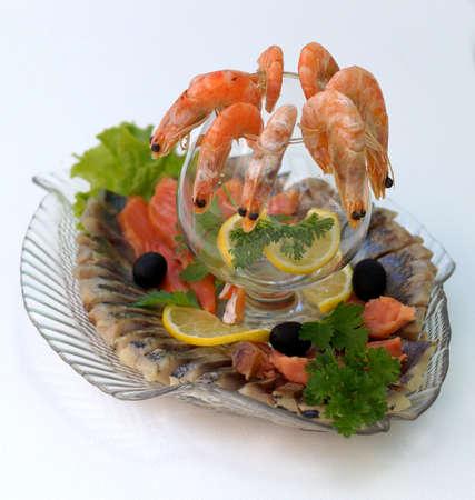 Gekochte Garnelen mit Zitrone und Petersilie auf einem Teller mit einer Auswahl an Fischgerichten. Lizenzfreie Bilder