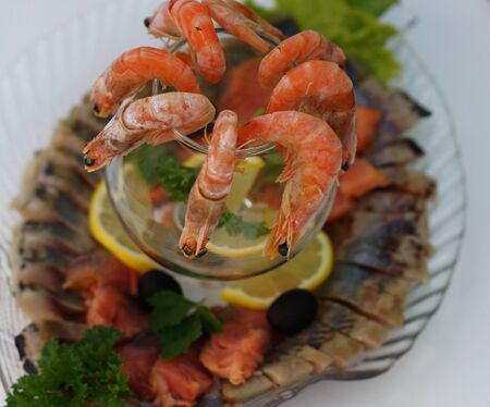 Boiled shrimps with lemon and parsley on a platter with an assortment of fish dishes.                           Stock Photo