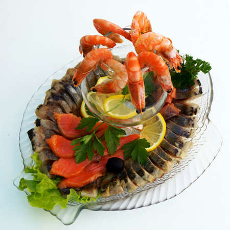 Boiled shrimps with lemon and parsley on a platter with an assortment of fish dishes.