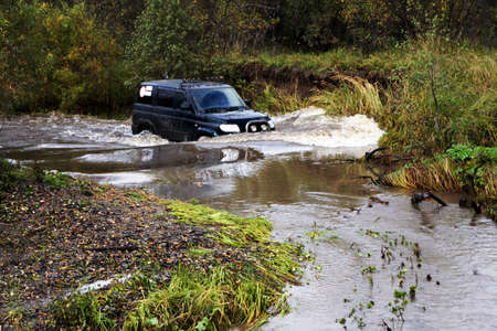 forest management: SUV moving a mountain river. Stock Photo