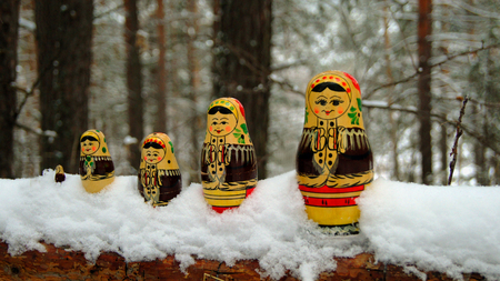 Russian souvenir matreshka on the trunk of a fallen tree in the winter forest.