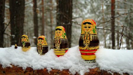 Russische Souvenir matreshka auf dem Stamm eines umgest�rzten Baumes in den Winterwald.