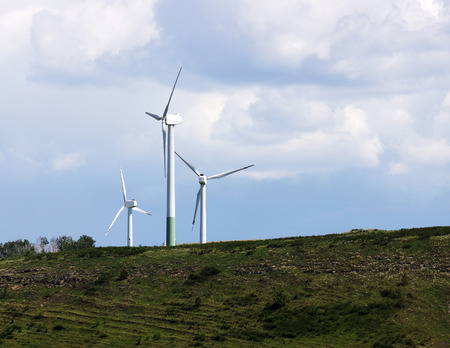 Wind energy generator is located on a hill on the background of a cloudy sky. Stock Photo