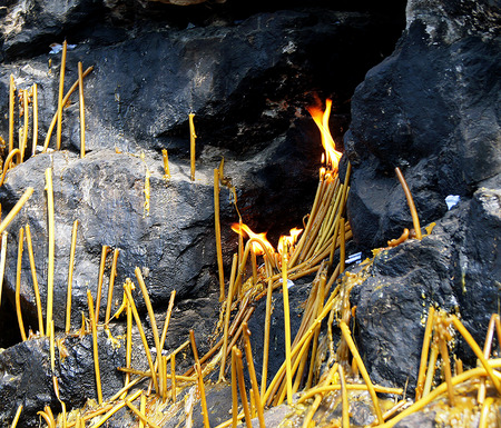 Lighted candles at the foot of the rock memory. Stock Photo