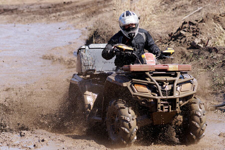 Extreme driving ATV on overcoming mud obstacles.