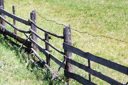rickety: The old rickety fence with broken planks and barbed wire. Stock Photo