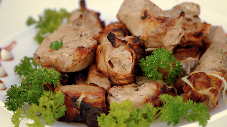 Fried meat  with the green of the parsley on a white background.