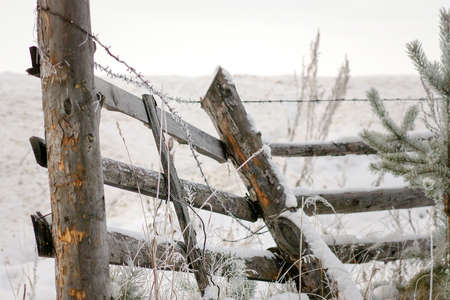The Old Rickety Fence With Broken Planks And Barbed Wire. Stock ...