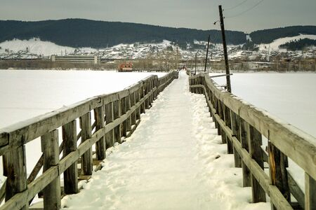 Old abandoned bridge over the river in the winter. Stock Photo