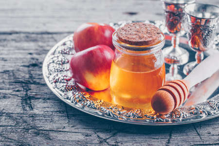 Honey Jar and Apples on beautiful tray on wooden table background. Jewish Holiday Rosh Hashanah Concept
