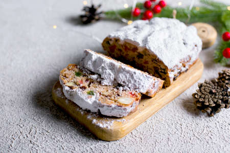 Christmas stollen on wooden tray on light concrete background. Traditional Christmas pastry dessert with festive decoration. Copy space Standard-Bild