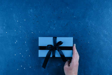 Blue gift box with sparkles on blue background. Holiday concept. Trend color of 2020 year. Top view, flat lay, copy space