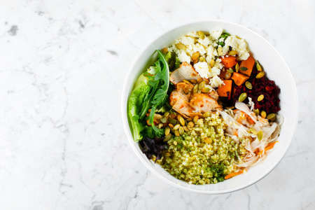 Top view of healthy pumpkin seasonal bowl. Salad with meat, cheese, bulgur and vegetables on marble background. Copy space