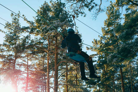 Man on a rope town (bridge) in an adventure rope park. Winter sport, leisure and outdoor games